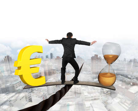Man standing on wood board between hourglass and golden euro sign, balancing on wire, with mist cityscape background. Time is money concept.