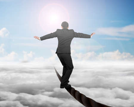 Businessman balancing on a wire with sky sub cloudscape background. Stock Photo