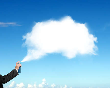 copy sapce: Male hand spraying white cloud paint on blue sky background