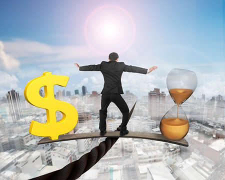 Man standing on wood board between hourglass and golden dollar sign, balancing on wire, with sky sun mist cityscape background. Time is money concept. Banco de Imagens