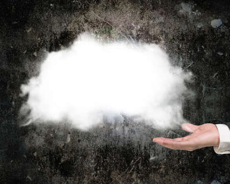 copy sapce: Male hand showing white cloud with dark concrete wall background