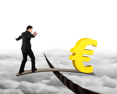 euro sign: Businessman and golden euro sign on wood board, balancing on wire, with cloudscape background.