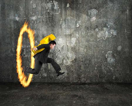 persona saltando: Empresario con signo de dólar de oro 3D, saltando a través del aro de fuego, con muro de hormigón en el interior oscuro y fondo piso.