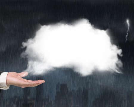 heavy rain: Male hand showing white cloud with heavy rain dark cityscape background