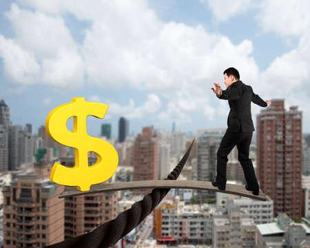 signo pesos: Hombre de negocios y signo de d�lar de oro en tablero de madera, el equilibrio en el alambre, con el cielo soleado fondo de la ciudad Foto de archivo