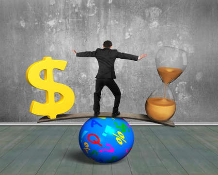 Man standing between hourglass and golden dollar sign, balancing on seesaw of wood board and colorful ball, with concrete wall and wooden floor indoors background. Time is money concept.