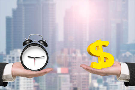 save time: Dollar sign on one hand and alarm clock on another hand, with sunlight city background, concept of deal and time. Stock Photo