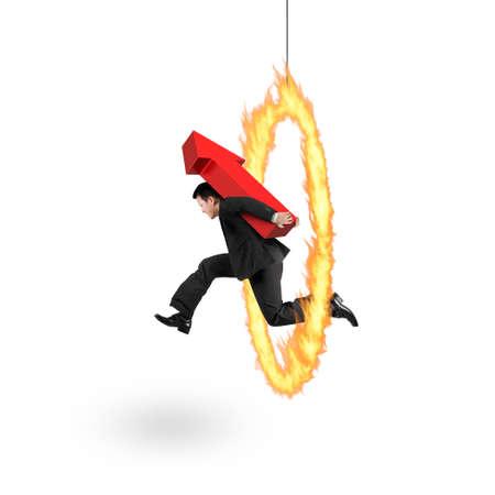 persona saltando: Empresario roja llevar 3D flecha arriba signo, saltando a través del aro de fuego, aislado en fondo blanco. Foto de archivo