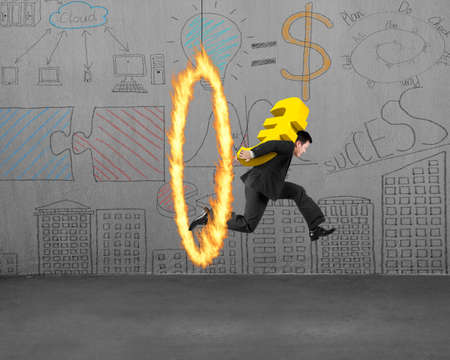 euro sign: Businessman carrying 3D golden euro sign, jumping through fire hoop, with doodles wall and concrete floor indoors background. Stock Photo
