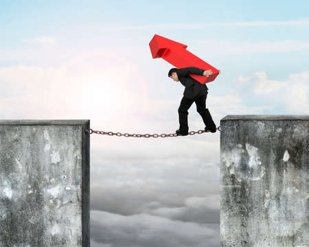 hard work ahead: Businessman carrying red arrow sign balancing on rusty chain connected two high dirty concrete walls, with sky sunlight clouds background.