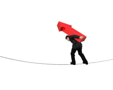 hard work ahead: Businessman carrying red arrow sign balancing on tightrope, with white background.