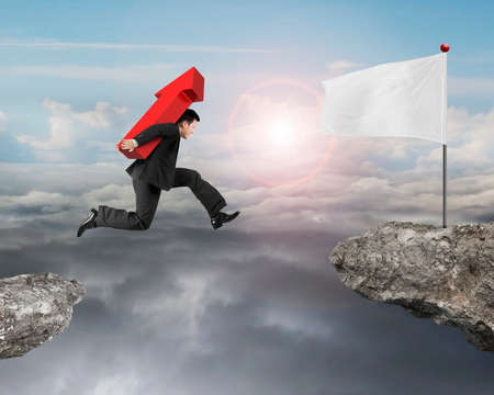 sun sky: Jumping businessman carrying 3D red arrow up sign to white flag on cliff, with sun sky cloudscape background.