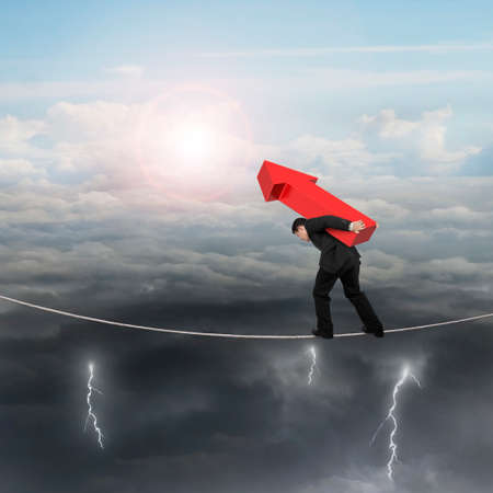 hard work ahead: Businessman carrying red arrow sign balancing on tightrope, with sky sun clouds background.