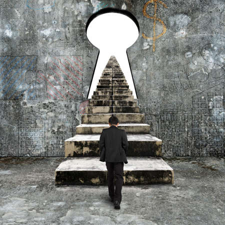 Man climbing old concrete stairs toward keyhole on concrete wall, with blank white view.