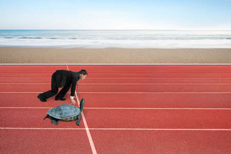 run faster: Businessman and turtle are ready to race on running track, with natural sea beach background. Turtle race competing metaphor concept.