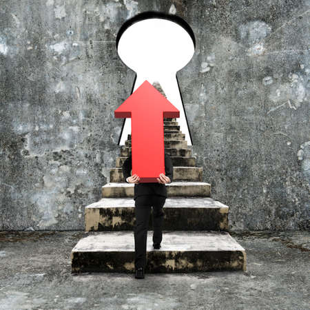 hard work ahead: Man carrying red arrow up sign climbing old concrete stairs toward keyhole, with blank white view.