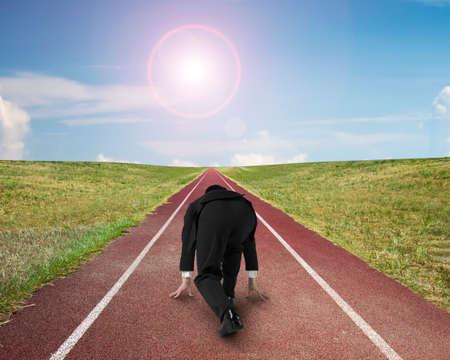 hombre deportista: Hombre de negocios listo para correr en la pista de atletismo, con el cielo sol nubes de fondo. Foto de archivo
