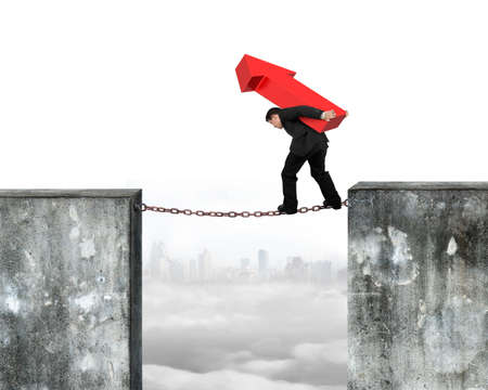 hard work ahead: Businessman carrying red arrow sign balancing on rusty chain connected two high dirty concrete walls, with urban skyline cloudscape background. Stock Photo