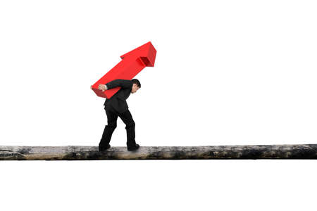 hard work ahead: Businessman carrying red arrow sign balancing on tree trunk, with white background.