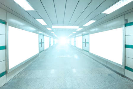 Bright underpass with blank billboard advertising wall for background.