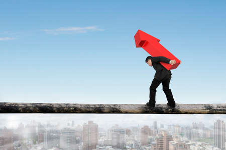 hard work ahead: Businessman carrying red arrow sign balancing on tree trunk, with sky city background. Stock Photo