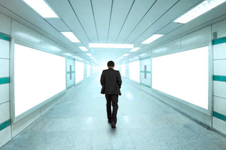 Rear view businessman walking through bright underpass, with blank billboard advertising wall.