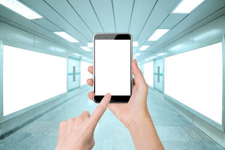 Woman hand holding smart phone, with finger touching blank white screen, front view, on bright underpass with billboard advertising wall background.