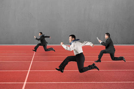 run faster: Three businessmen running on red track, with gray concrete wall background. Stock Photo