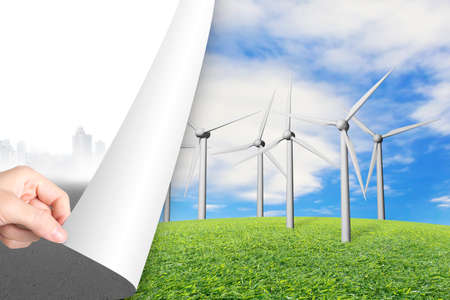 turning page: Woman hand turning gray cityscape page revealing group of wind turbines, alternative energy concept. Stock Photo