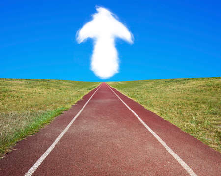 upward struggle: Arrow up shape cloud in blue sky, with dark red running track and grass.