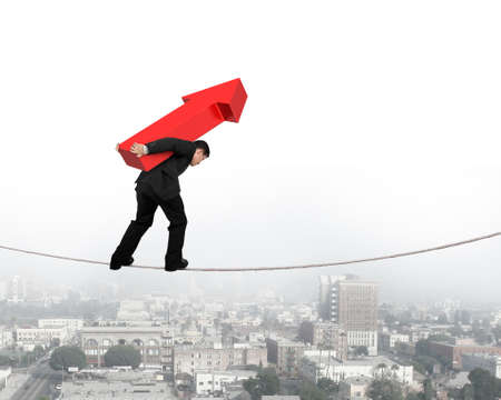hard work ahead: Businessman carrying red arrow sign balancing on tightrope, with city background.