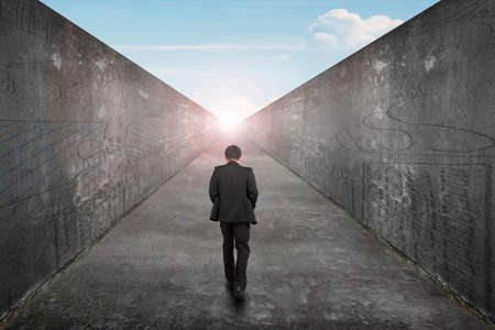 Businessman walking on one way road toward the exit of sun sky view, with high dirty concrete wall background. Standard-Bild
