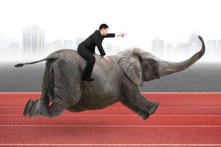 Businessman with pointing finger gesture riding on elephant, with city skyline and red track background.