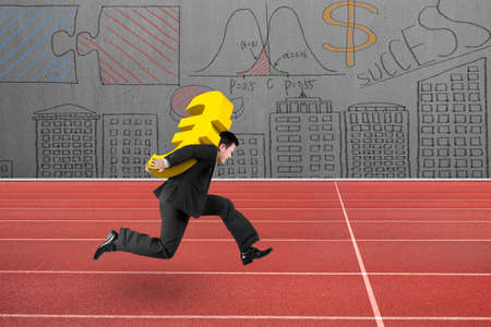 euro sign: Businessman carrying 3D golden euro sign running on red track, with business concepts doodles wall background.