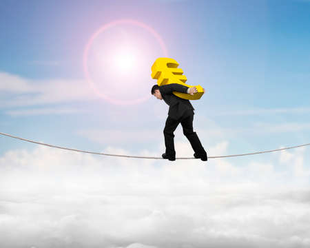 euro sign: Businessman carrying golden euro sign balancing on tightrope, with sky sun clouds background.