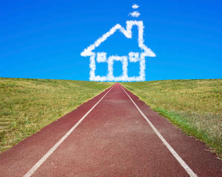 toward: House shape clouds in blue sky, with dark red running track and grass. Stock Photo