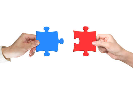 two piece: Man and woman hands assembling different color puzzle pieces, isolated on white. Teamwork concept. Stock Photo