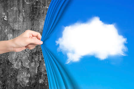 Woman hand pulling open white cloud blue curtain covering old mottled concrete wall. Stock Photo