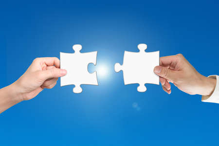 Man and woman two hands assembling jigsaw puzzle pieces, with blue background. Teamwork concept. Stock Photo