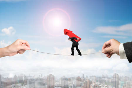 hard work ahead: Businessman carrying red arrow sign, balancing on tightrope with man and woman hands holding two sides, on sun sky city landscape background. Stock Photo