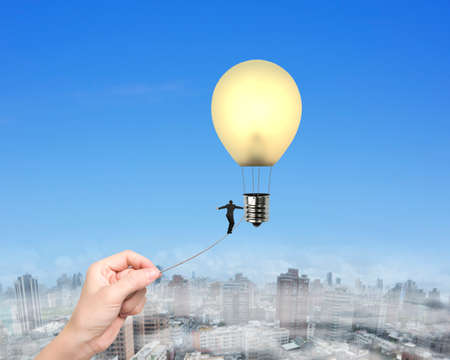 dream vision: Businessman walking tightrope woman hand pulling, toward yellow lightbulb shape hot air balloon, with natural sky urban scene background. Stock Photo