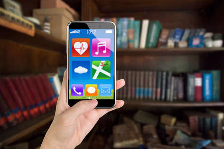 button front: Female hand holding app icons smartphone with thumb pushing button, front view, on bookshelf background.