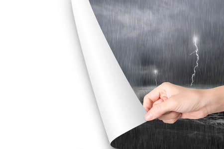 storm sky: Woman hand open blank white page to replace dark stormy ocean