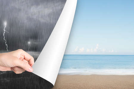 flip: Woman hand open calm sea beach page to replace dark stormy ocean Stock Photo