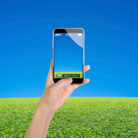button grass: Woman hand holding smart phone, with thumb pushing button, front view, on blue sky and grass background.