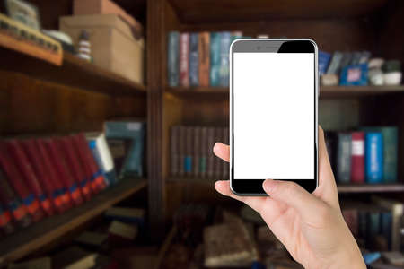 pushing button: Woman hand holding blank white screen smart phone, with thumb pushing button, front view, on bookshelf background.