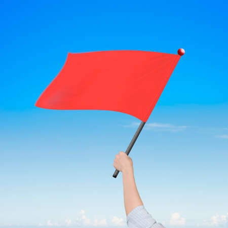 overcome a challenge: Woman hand holding blank red flag, on nature sky clouds background. Stock Photo