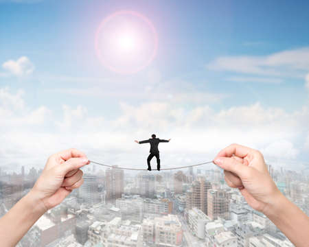 overcome a challenge: Businessman balancing on tightrope with woman two hands holding two sides, on sunny sky cityscape background.