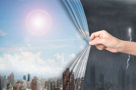 heavy risk: Woman hand pulling open sunny sky cityscape curtain covering stormy city.