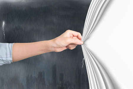 Female hand pulling open blank white curtain covering stormy city.
